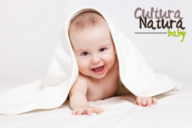 An adorable, laughing baby looking at camera under a white blanket