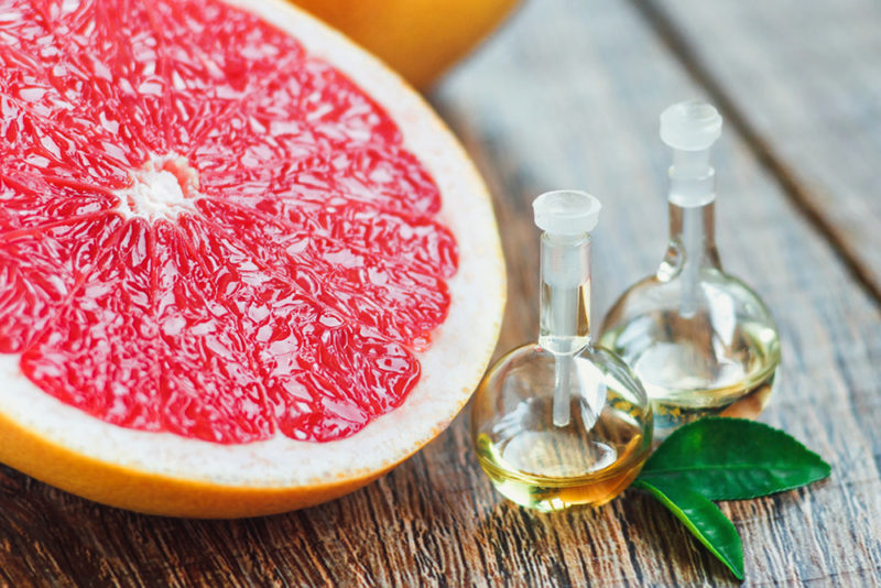 Essential oil in glass bottle with fresh, juicy grapefruit and g