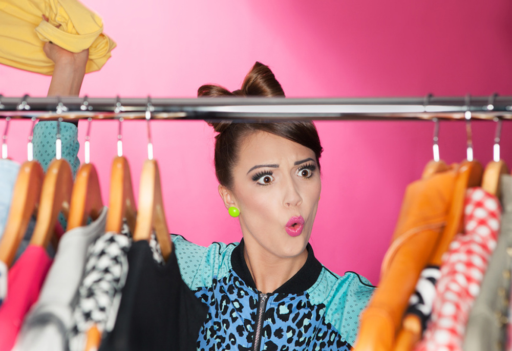 Young surprised woman searching for clothing in a closet