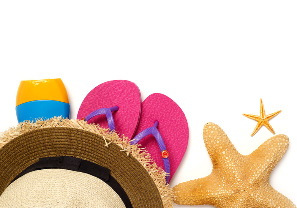 Straw hat, sun lotion, flip-flops and starfish isolated on white